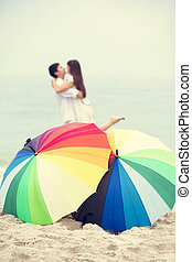 Couple kissing at the beach with umbrella