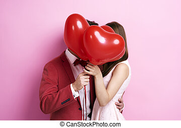 Couple kissing behind balloons