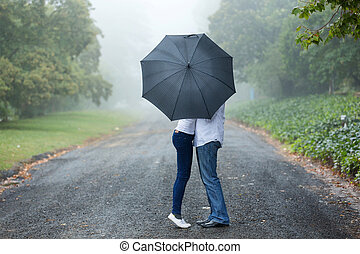 couple kissing behind the umbrella