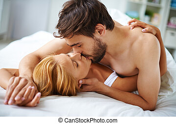 Couple kissing - Hands of female and male lying on bed and...