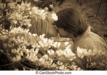couple kissing in dogwood blossoms