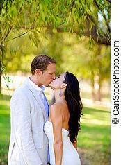 couple kissing in honeymoon outdoor park