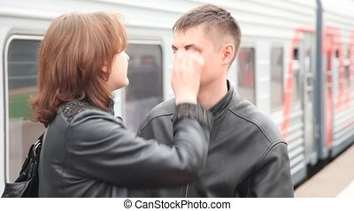 couple kissing in railroad station, train on background
