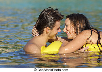 Couple kissing in summer vacation on the beach