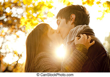 Couple kissing in the park at sunset