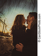 Couple kissing in the park at sunset. Photo in multicolor image style.