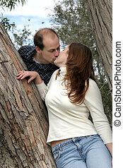 Couple Kissing In Tree - A young married couple kiss while...