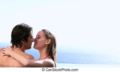 Couple kissing next to a swimming p