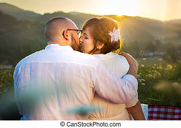 Couple kissing on picnic with sunset view
