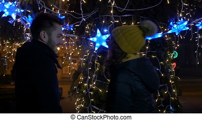 Couple kissing outside in a park near Christmas Tree
