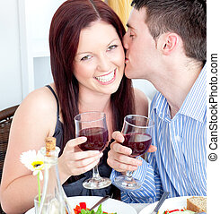 couple kissing while drinking wine