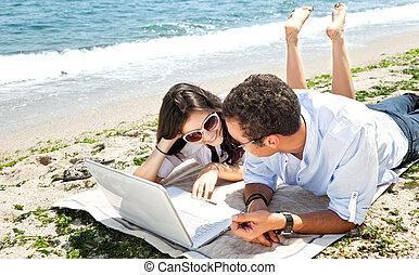 Couple laptop beach
