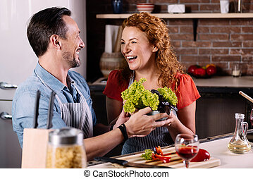 Couple laughing and cooking vegetables