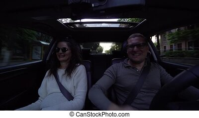 Couple laughing and cuddling in car driving