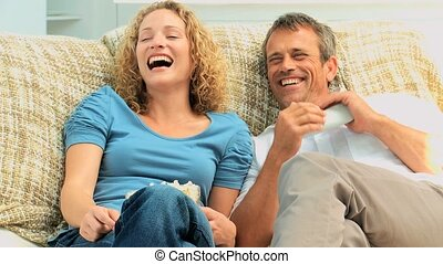 Couple laughing in front of the tv with popcorn