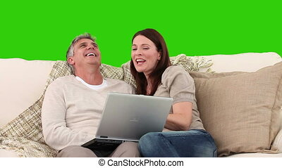 Couple laughing in front of their laptop