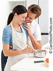 Couple laughing while preparing a sauce in the kitchen