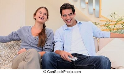 Couple laughing while watching televison