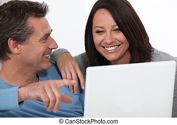 Couple laughing whilst looking at laptop screen