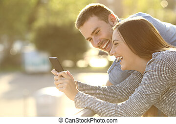 Couple laughing with media content in a phone - Side view of...