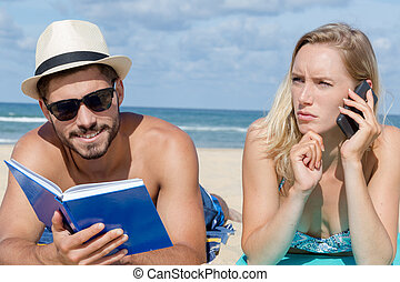 couple layed on beach man readying book woman on cellphone