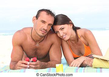 Couple laying on beach towel