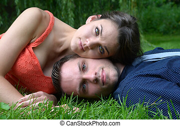 Couple laying on grass in garden