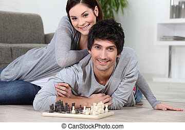 Couple laying on the floor playing chess