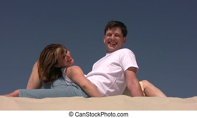 Couple laying on the sand, looks at each other