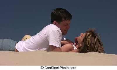 Couple laying on the sand, she caress his face