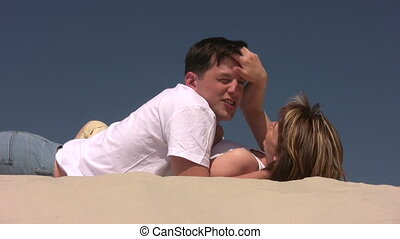 Couple laying on the sand, she plays with his hair