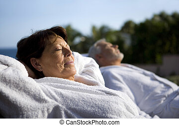 Couple laying outside in bathing robes