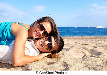 Couple laying together on beach.