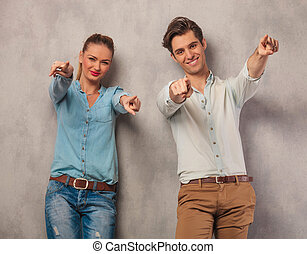 couple leaning on a wall while pointing their fingers