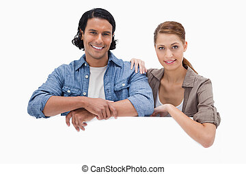 Couple leaning on blank wall