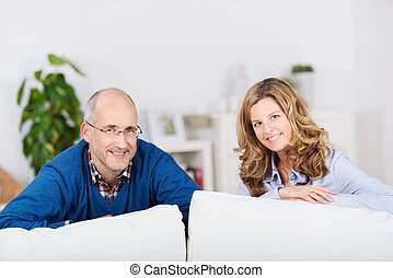 Couple Leaning On Sofa At Home