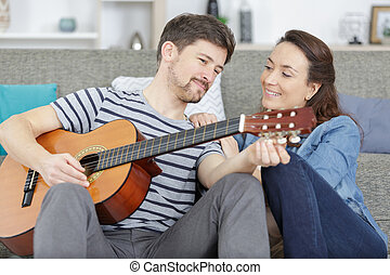 couple learning how to play guitar