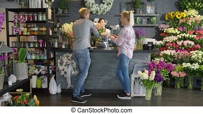 Couple leaving shop with bouquet - Young man leaving flower...