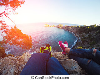 Couple legs hanging over rocks