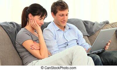couple, leur, désinvolte, regarder, ordinateur portable