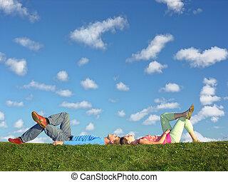 couple lies under clouds