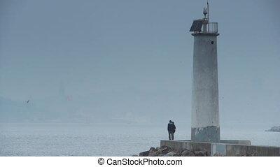 Couple lighthouse coast sea
