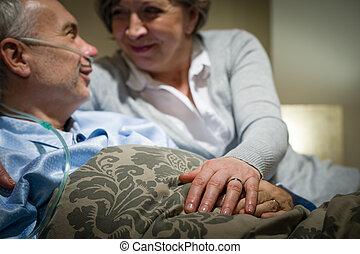 couple, lit, personnes agées, tenant mains, mensonge
