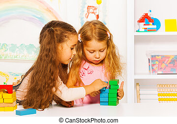 Couple little girls playing stacking wooden blocks