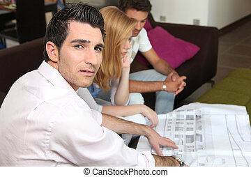 Couple looking at a blueprint with their architect