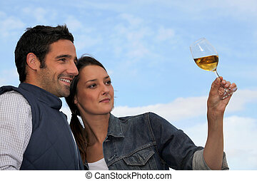 Couple looking at a glass of wine