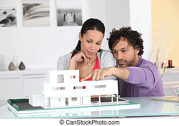 Couple looking at an architect model of a new development