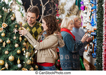 Couple Looking At Christmas Tree With Parents In Background