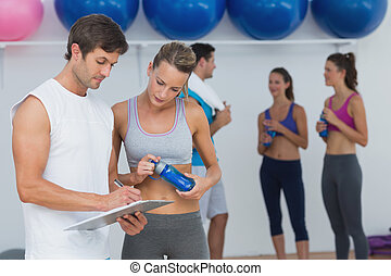 Couple looking at clipboard with fitness class in background...