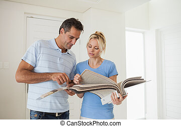 Couple looking at color book in house